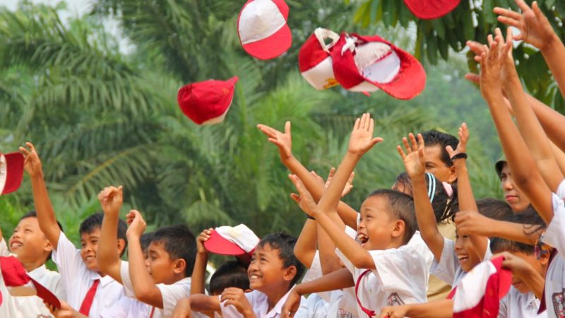 Tanoto Foundation Children celebrate by throwing caps in the air.